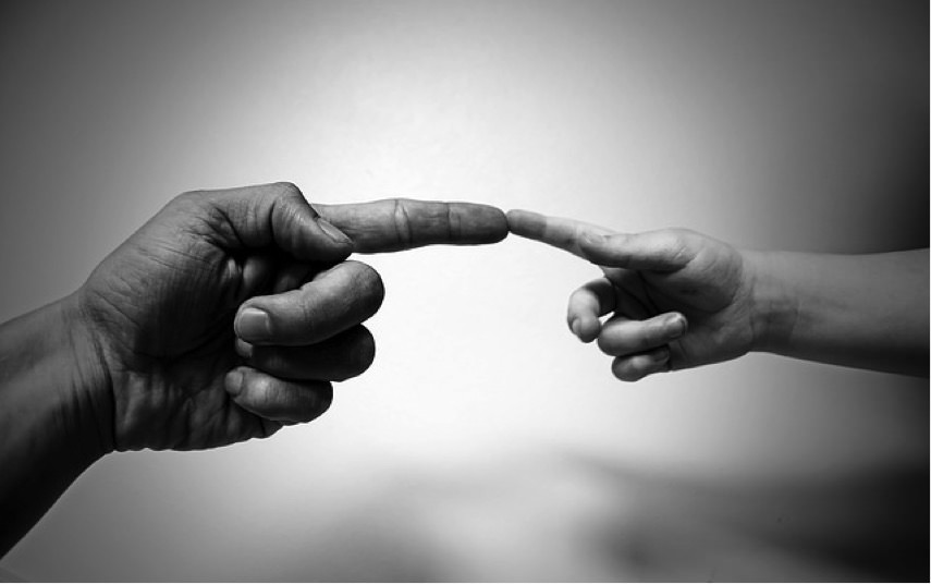 Large hand reaches out to touch fingers with a small hand