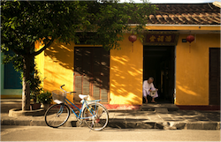 Chinese man reading newspaper with bicycle parked outside