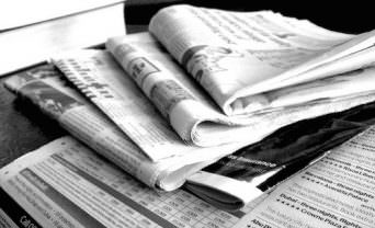 photo of folded newspapers on a table